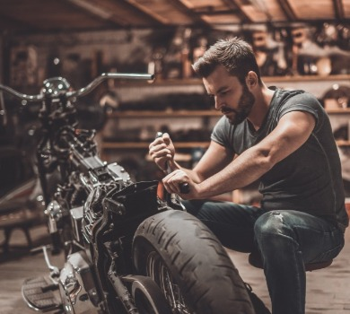 man performing pre-trip motorcycle tune up | Asheville Connections