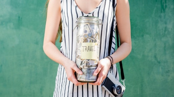 Woman holding a jar labeled Travel with money in it | Asheville Connections