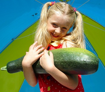 Little girl holding a cucumber atfarmers' market in Asheville NC
